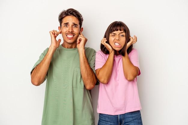 Młoda para rasy mieszanej na białym tle zakrywająca uszy palcami, zestresowana i zdesperowana przez głośne otoczenie.