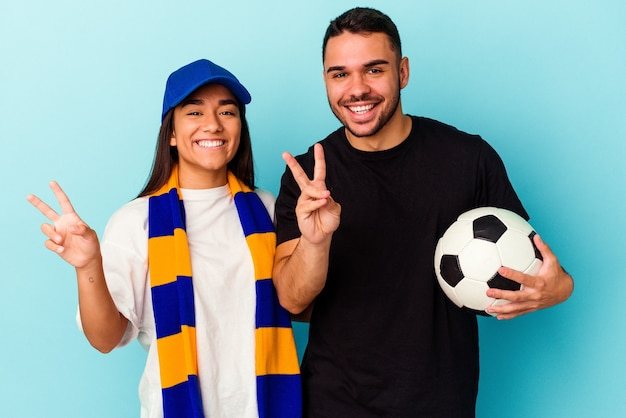 Młoda para rasy mieszanej, sprzątanie domu na białym tle na niebieskim tle pokazując numer dwa palcami.