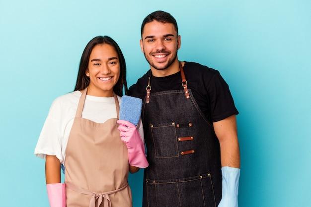 Młoda para rasy mieszanej sprzątanie domu na białym tle na niebieskim tle szczęśliwa, uśmiechnięta i wesoła.