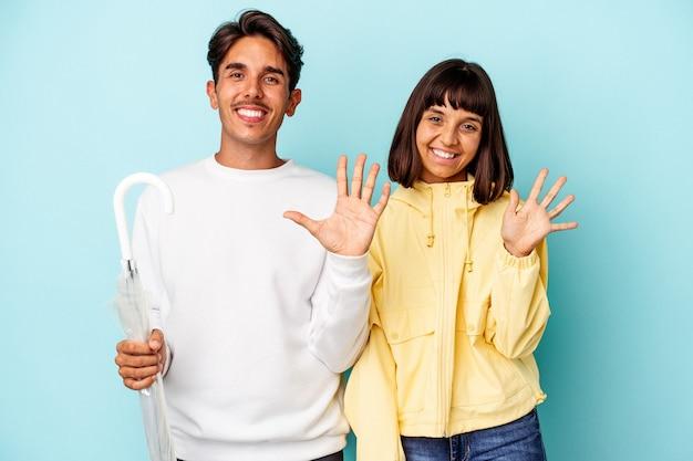 Młoda para rasy mieszanej trzymając parasol na białym tle na niebieskim tle uśmiechnięty wesoły pokazano numer pięć palcami.
