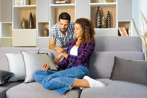 Młoda para razem oglądając multimedia na tablecie, relaksując się w salonie w domu w ramach osobistej koncepcji rozrywki