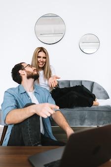Młoda para razem przy użyciu komputera przenośnego i odpoczynku na kanapie w domu.