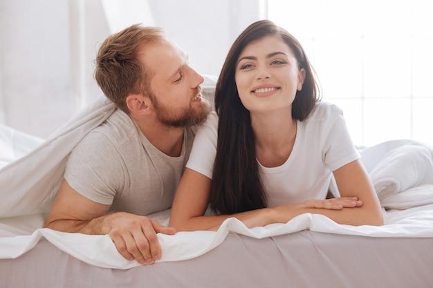 Młoda para relaksując się w łóżku i rozmawiając pod kocem w domu