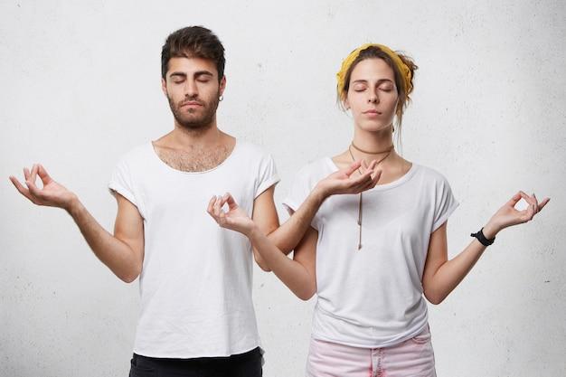 Młoda para relaksujący medytacji stojąc przed białą ścianą