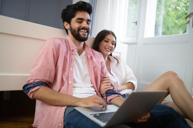 Młoda para relaksuje na łóżku z laptopem. koncepcja miłości, technologii, szczęścia, ludzi i zabawy.