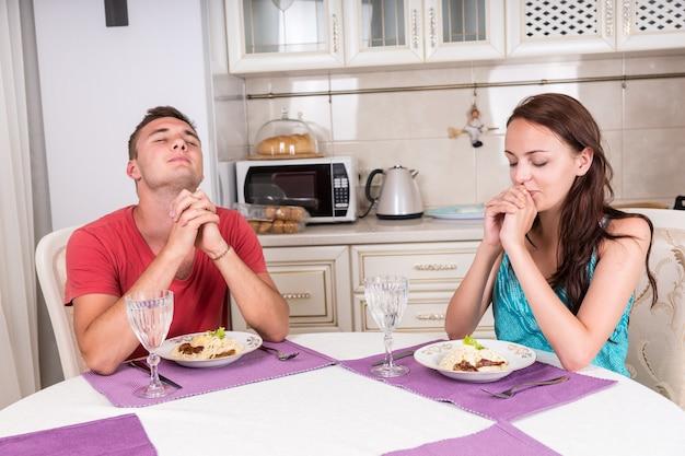 Młoda para religijna odmawiająca modlitwę łaski przed jedzeniem ugotowanego w domu posiłku przy stole jadalnym w kuchni małego domu