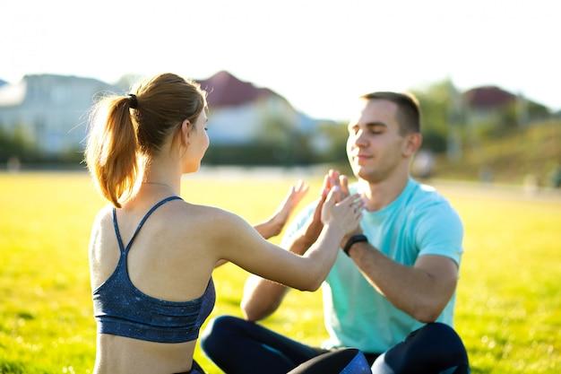 Młoda para robi ćwiczenia jogi fitness w ciepły letni dzień