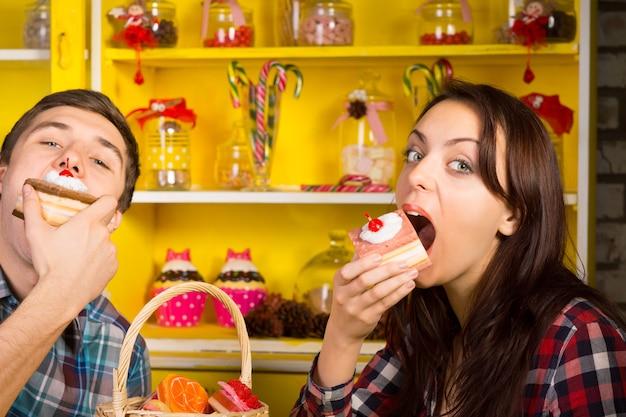 Młoda para robi jedzenie ciasta stanowią w kawiarni, patrząc w kamerę. zrobione z candy jars display z tyłu.