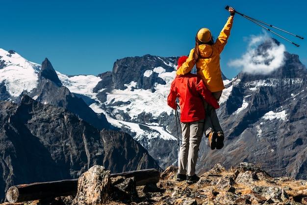 Młoda para robi nordic walking w górach, widok z tyłu. aktywna para zajmuje się pieszymi wędrówkami. młoda para zajmuje się tropieniem. trekking i nordic walking. wędrówki. skopiuj miejsce