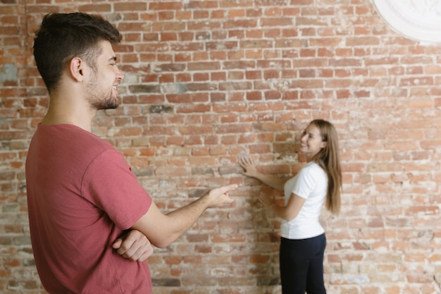 Młoda para robi razem remont mieszkania. żonaty mężczyzna i kobieta robią remont lub remont domu