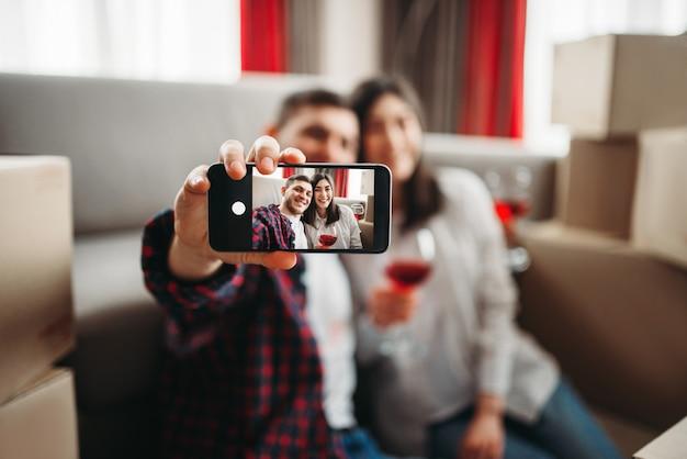 Młoda para robi selfie na tle kartonowych pudełek, przeprowadzając się do nowego domu. przeprowadzka na uroczystość w mieszkaniu