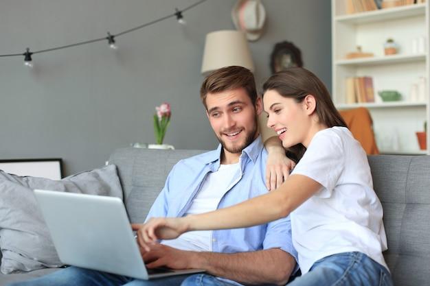 Młoda para robi zakupy online w domu, korzystając z laptopa na kanapie.