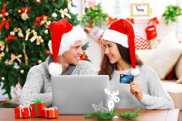 Młoda para robi zakupy online z kartą kredytową w domu na boże narodzenie