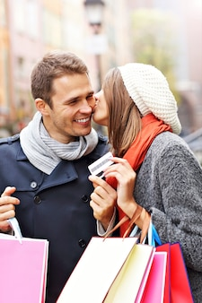 Młoda para robi zakupy w mieście za pomocą karty kredytowej
