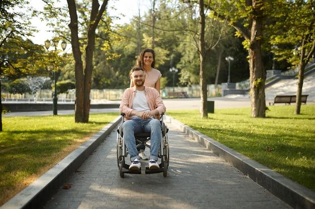 Młoda para rodzina z wózka inwalidzkiego spaceru w parku. osoby sparaliżowane i niepełnosprawne, opieka nad niepełnosprawnym mężczyzną. mąż i żona wspólnie pokonują trudności, ciepłe relacje