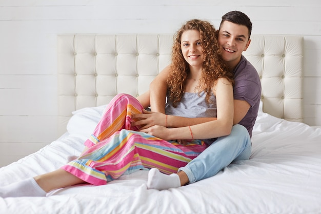Młoda para rodzinna siedzi i obejmuje się na wygodnym łóżku, cieszy się wspólnością i dzień dobry, ma pozytywne miny, nosi piżamę. kręcona piękna kobieta spędza wolny czas w sypialni z kochankiem