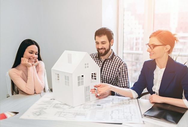 Młoda para rodzinna zakup nieruchomości na wynajem nieruchomości. agent udzielający konsultacji mężczyźnie i kobiecie. podpisanie umowy na zakup domu lub mieszkania lub mieszkania. w rękach trzyma model domu