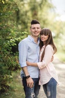 Młoda para romantyczny bawi się w słoneczny letni dzień w parku. wspólne spędzanie czasu na wakacjach. mężczyzna i kobieta są przytuleni i uśmiechnięci.