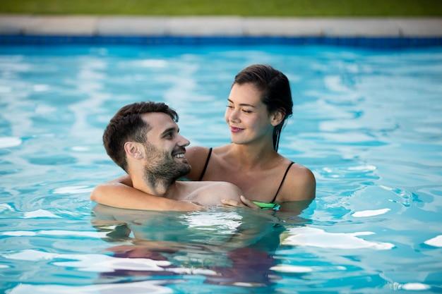 Młoda para romantyczny, obejmując się w basenie