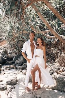Młoda para romantyczny w białych ubraniach przytulanie i pozowanie na gorącej tropikalnej plaży