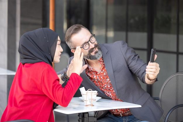 Młoda para romantyczny w restauracji siedzi, robienie zdjęć