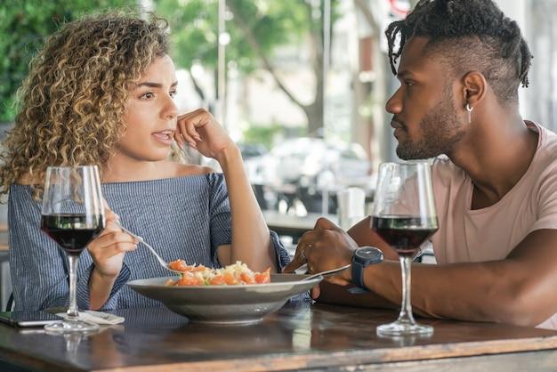 Młoda para rozmawia i cieszy się podczas wspólnego obiadu w restauracji.