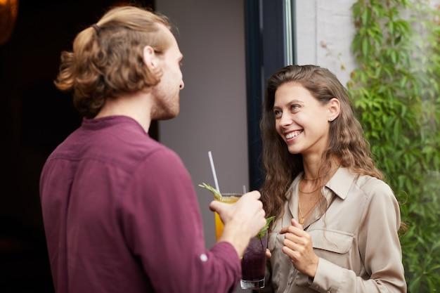 Młoda para rozmawia na zewnątrz przez cafe