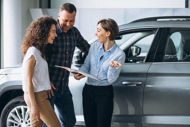 Młoda para rozmawia z handlowcem w salonie samochodowym