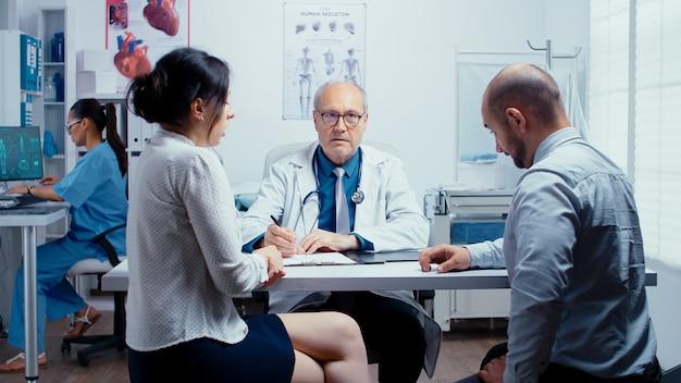 Młoda para rozmawia ze starszym lekarzem w nowoczesnej prywatnej klinice. specjalista ds. planowania rodziny. osoby w nowoczesnym prywatnym szpitalu lub klinice, problemy z medycyną i opieką zdrowotną.