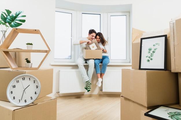 Młoda para rozpakowywanie kartonów w ich nowym domu