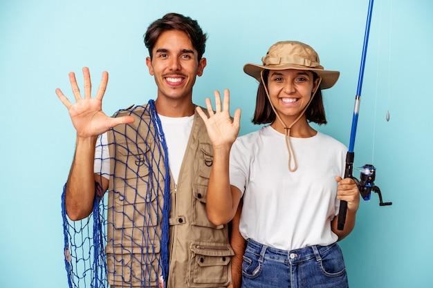 Młoda para rybak rasy mieszanej na białym tle na niebieskim tle uśmiechający się wesoły pokazując numer pięć palcami.
