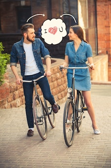 Młoda para siedząca na rowerze naprzeciwko miasta