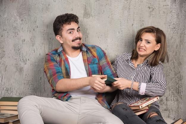Młoda para siedzi i biorąc książkę od siebie