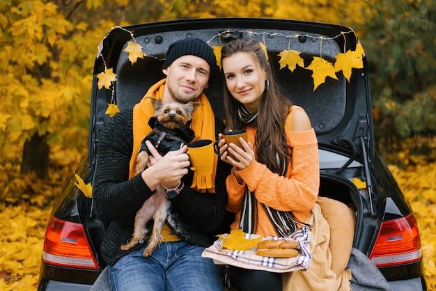 Młoda para siedzi na bagażniku samochodu