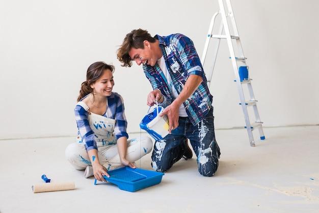 Młoda para siedzi na białej podłodze i wlewa farbę