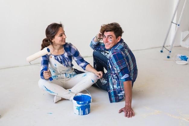 Młoda para siedzi na białej podłodze.
