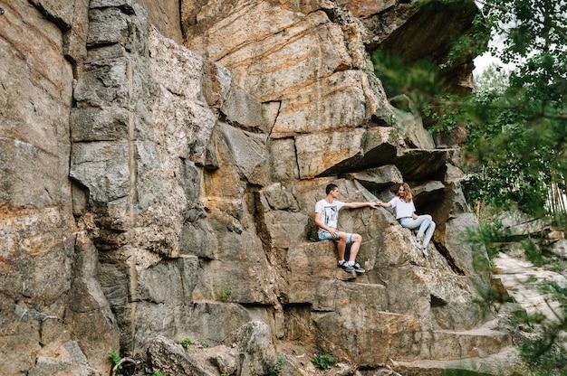 Młoda para siedzi na kamiennym murem. widok z boku. pełna długość. patrząc w dół