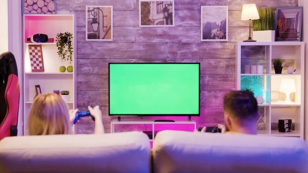 Młoda para siedzi na kanapie i gra w gry online na telewizorze z zielonym ekranem. szczęśliwy związek. para graczy.
