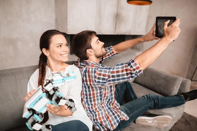 Młoda para siedzi na kanapie i robi selfie.