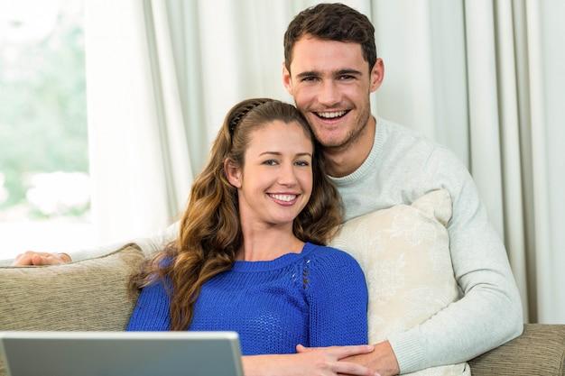 Młoda para siedzi na kanapie i za pomocą laptopa w salonie