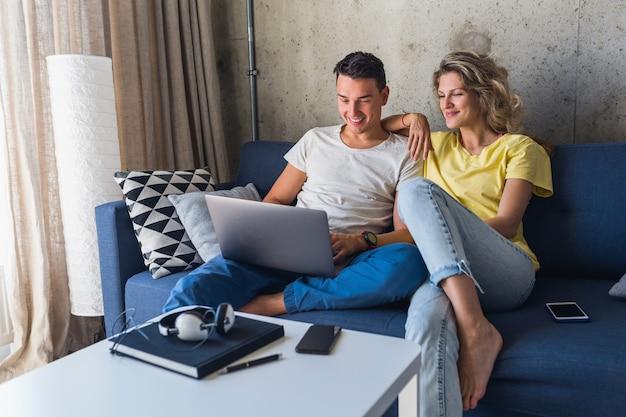 Młoda para siedzi na kanapie w domu, patrząc w laptopa, oglądając filmy online, korzystając z internetu