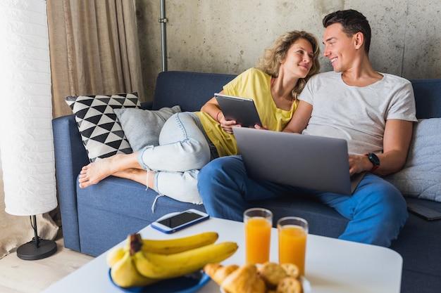 Młoda para siedzi na kanapie w domu, patrząc w laptopa