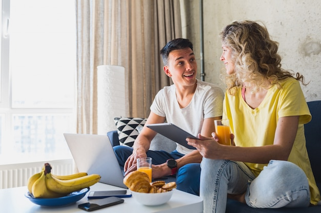 Młoda para siedzi na kanapie w domu, pracując online na laptopie i tablecie