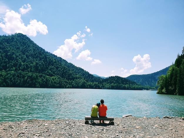 Młoda para siedzi na ławce na tle jeziora ritsa w abchazji w słoneczny letni dzień