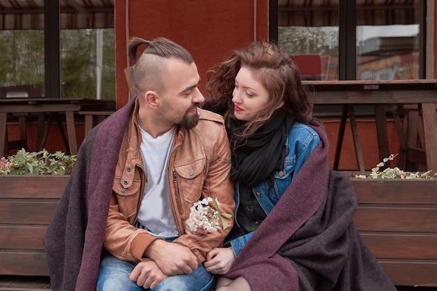 Młoda para siedzi na ławce w pobliżu ulicznej kawiarni. historia miłosna