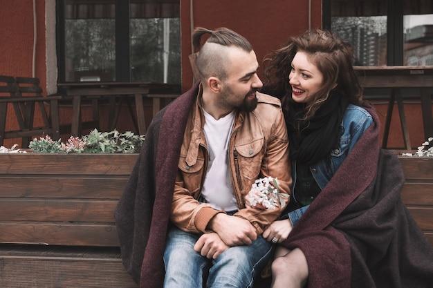 Młoda para siedzi na ławce w starej historii miłosnej ulicy miasta