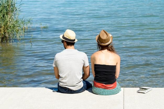 Młoda para siedzi na nabrzeżu, widok z tyłu