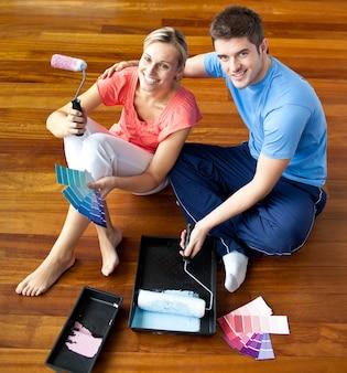 Młoda para siedzi na podłodze z uśmiechem