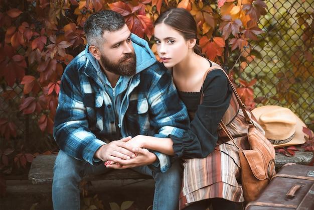 Młoda para siedzi na świeżym powietrzu w parku jesienią.
