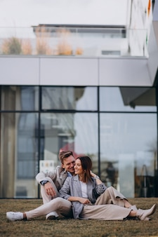 Młoda para siedzi na trawie przez budynek
